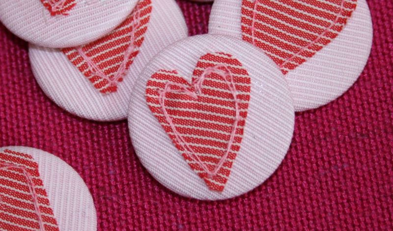Heart badges close up on group on pink